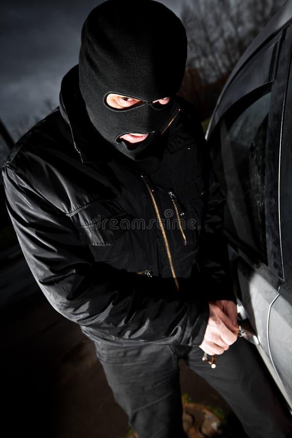 Le voleur et le voleur dans un masque détourne le véhicule images stock