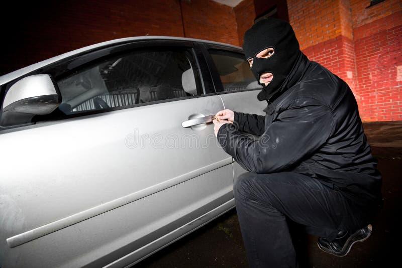 Le voleur et le voleur dans un masque détourne le véhicule image stock