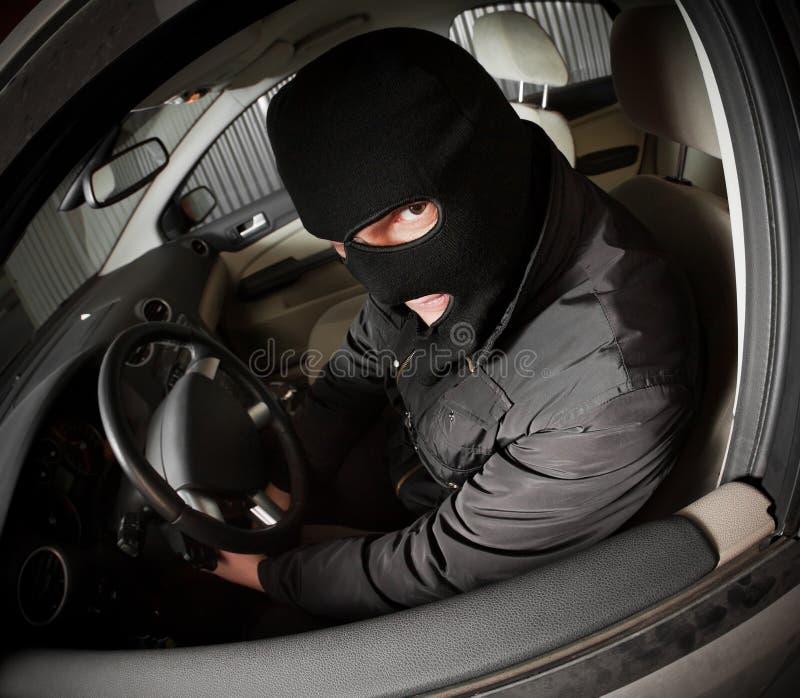 Le voleur et le voleur dans un masque détourne le véhicule images libres de droits