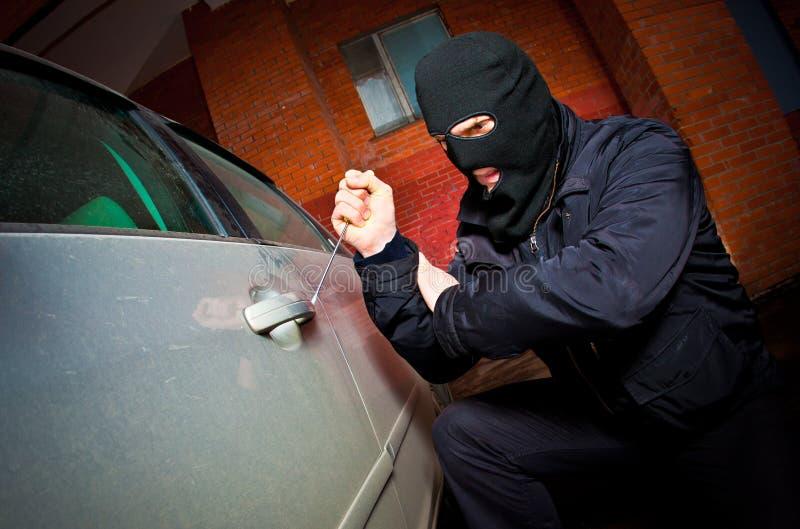 Le voleur et le voleur dans un masque détourne le véhicule photos stock