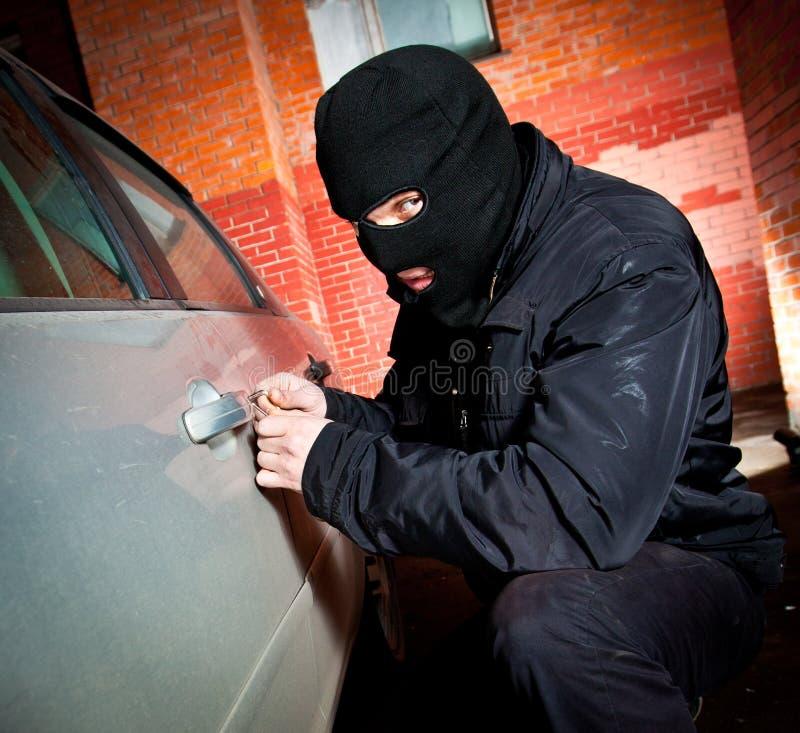 Le voleur et le voleur dans un masque détourne le véhicule photographie stock libre de droits