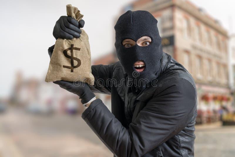 Le voleur heureux montre le sac volé complètement de l'argent image libre de droits