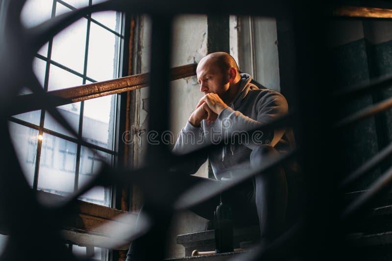 Le voleur masculin avec la bouteille d'alcool s'assied sur des escaliers image stock
