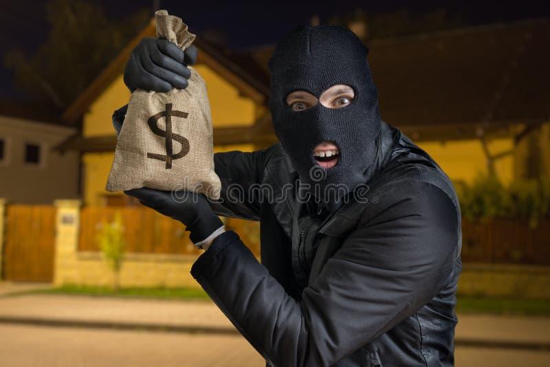 Le voleur ou le cambrioleur heureux montre le sac volé complètement de l'argent la nuit photo libre de droits