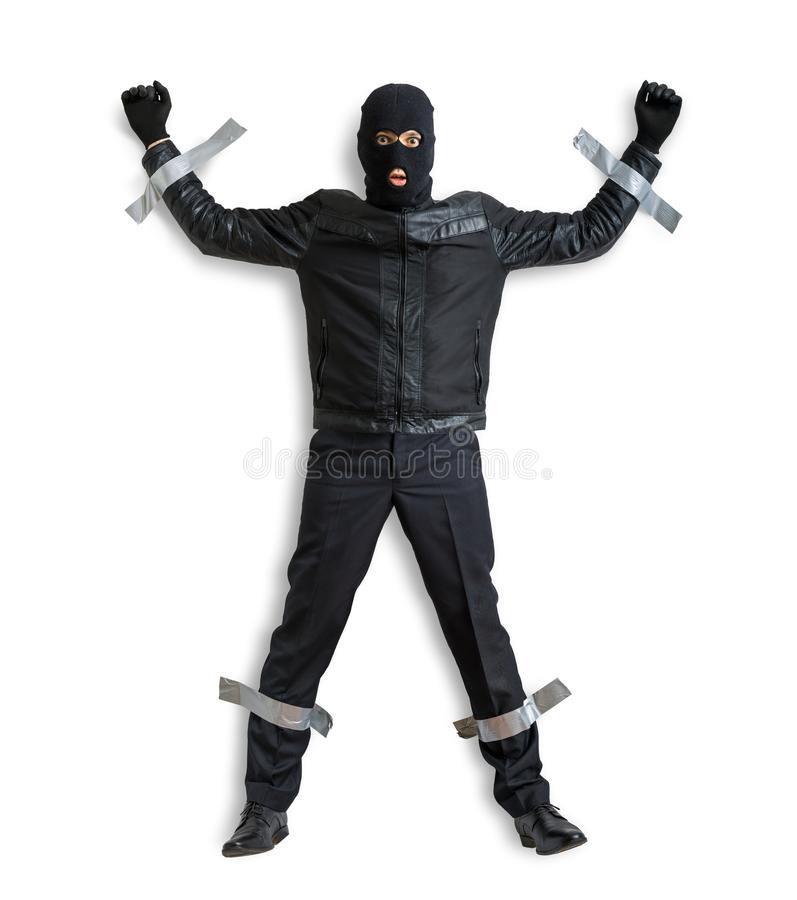 Le voleur ou le cambrioleur masqué avec le passe-montagne est attrapé et est attaché du ruban adhésif au mur avec le ruban adhési images stock