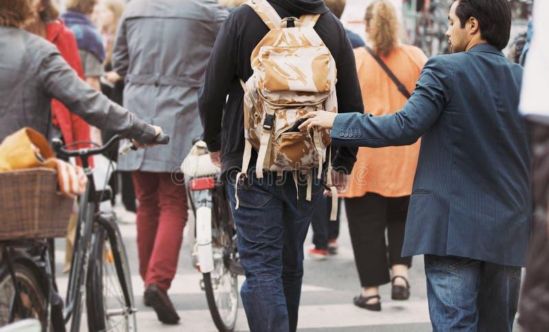 Le voleur tire le portefeuille hors d'un sac à dos d'homme photos libres de droits