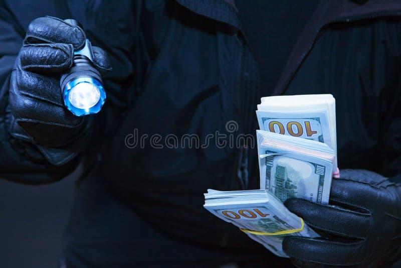 Le voleur vole l'argent dans l'obscurité photo stock