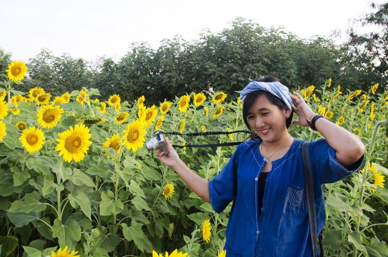 Le voyage thaïlandais asiatique de femme et la pose pour prennent la photo au gisement de tournesol photos stock