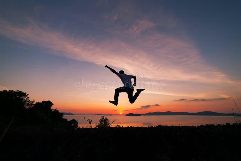 Le voyageur asiatique d'homme saute sur une montagne de forêt tropicale dedans image stock