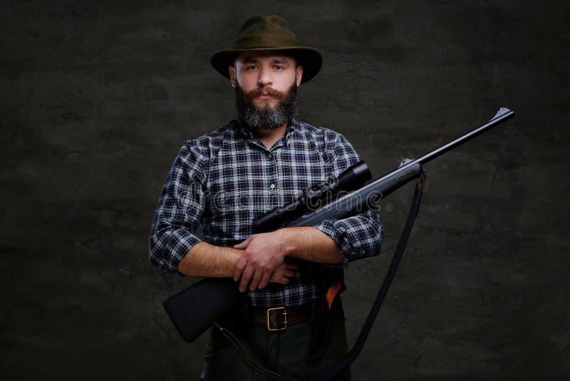 Le voyageur barbu beau de chasseur dans des prises d'une chemise et de chapeau d'ouatine fusillent avec une vue photos stock