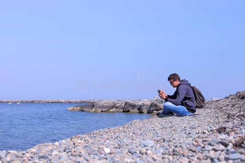 Le voyageur d'homme s'assied sur la plage de pierre de mer et le smartphone de lecture rapide, vue de côté photo libre de droits