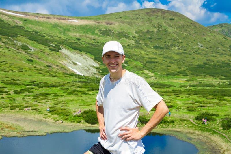 Le voyageur d'homme sur des montagnes s'approchent du lac photos stock