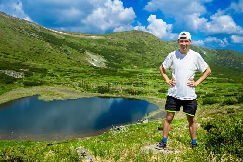 Le voyageur d'homme sur des montagnes s'approchent du lac images libres de droits