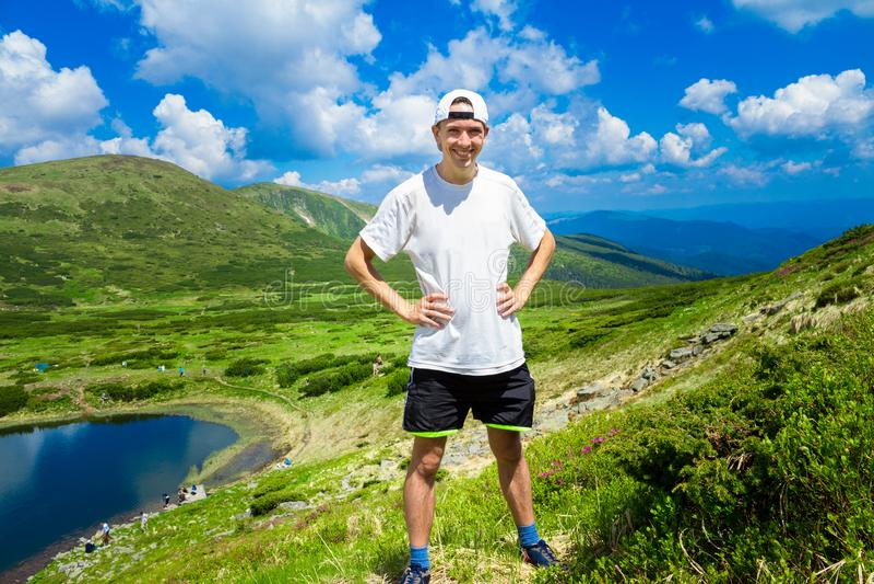 Le voyageur d'homme sur des montagnes s'approchent du lac image stock