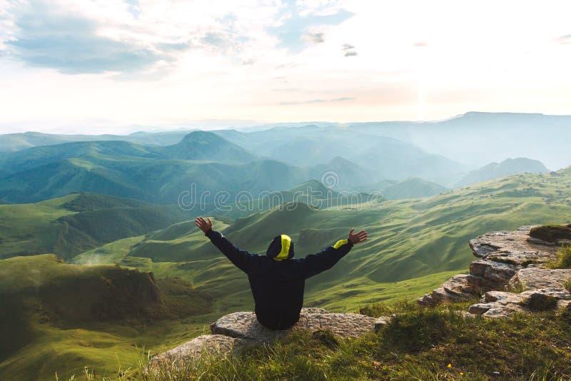 Le voyageur d'homme sur le sommet de montagne appréciant des mains de vue aérienne a soulevé des vacances actives d'aventure de c images stock