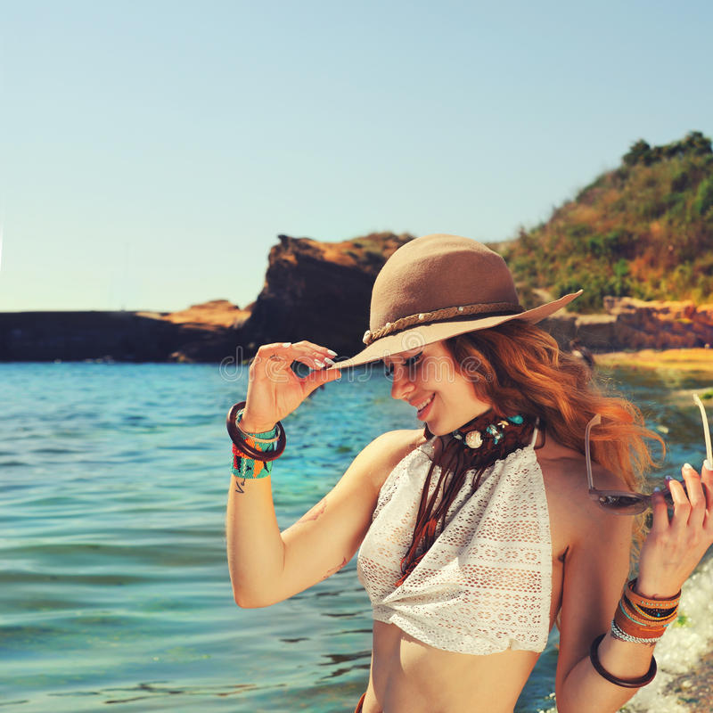 Le voyageur de femme trimardant près de la plage de mer, souriant et beau, s'est habillé dans les bracelets chics et le chapeau d image stock