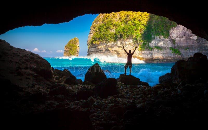 Le voyageur de jeune homme apprécient la vue étonnante de matin de la falaise raide et de l'océan à la plage tropicale image libre de droits