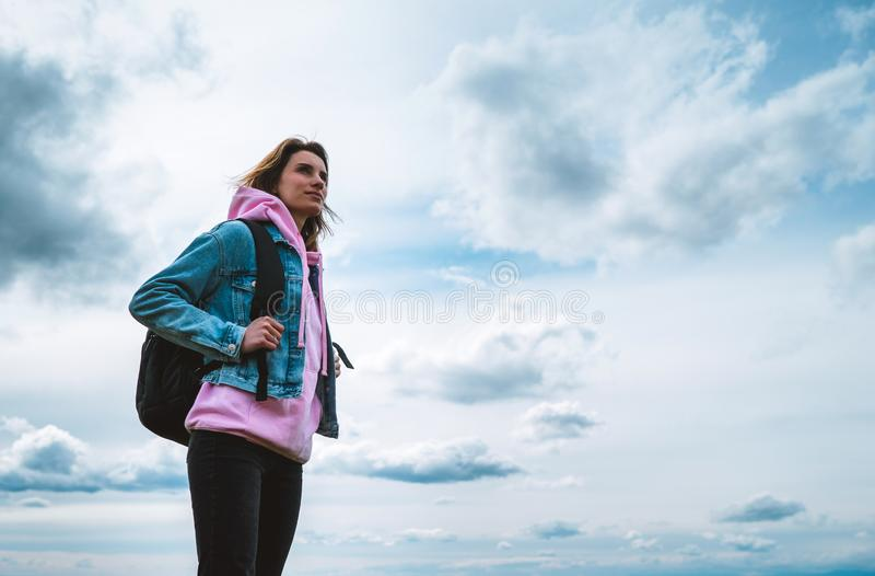 Le voyageur de touristes avec le sac à dos noir sur la montagne de fond, randonneur regarde des nuages de ciel bleu, fille appréc photo stock