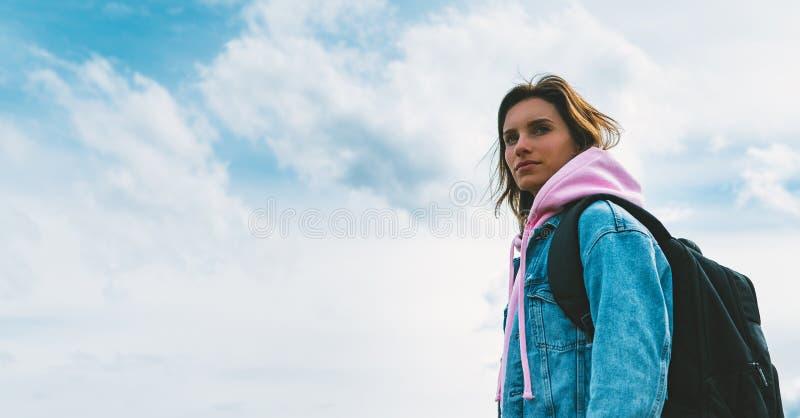 Le voyageur de touristes avec le sac à dos noir sur la montagne de fond, randonneur regarde des nuages de ciel bleu, fille appréc photographie stock libre de droits