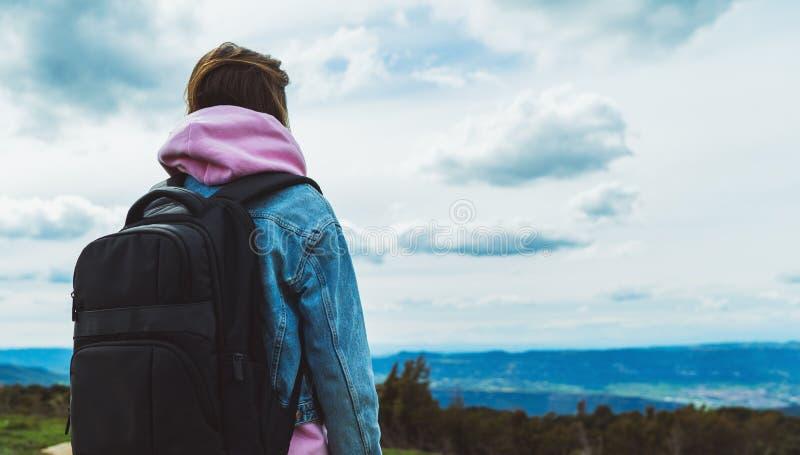 Le voyageur de touristes avec le sac à dos noir sur la montagne de fond, randonneur regarde des nuages de ciel bleu, fille appréc image stock