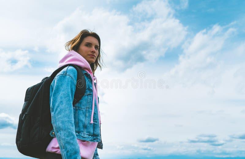 Le voyageur de touristes avec le sac à dos noir sur la montagne de fond, randonneur regarde des nuages de ciel bleu, fille appréc photographie stock