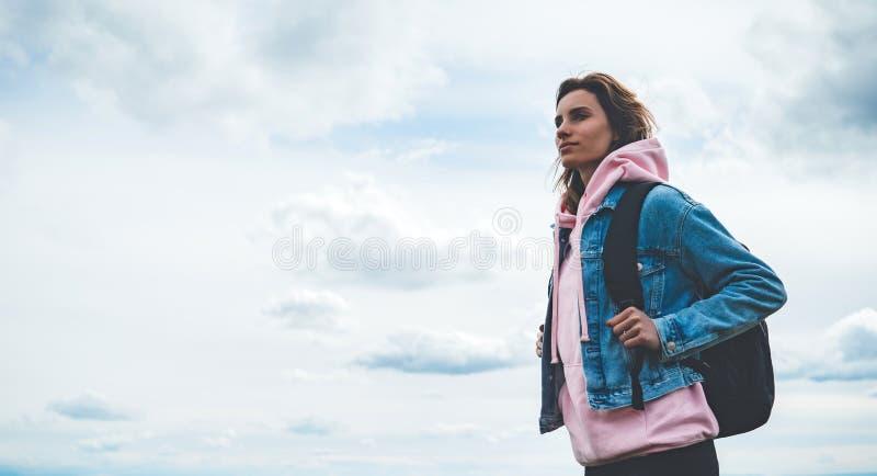 Le voyageur de touristes avec le sac à dos noir sur la montagne de fond, randonneur regarde des nuages de ciel bleu, fille appréc photo libre de droits
