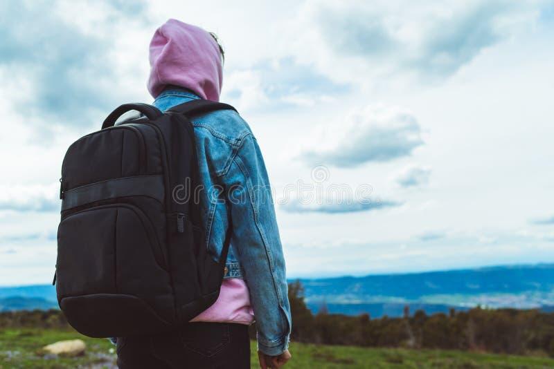 Le voyageur de touristes avec le sac à dos noir sur la montagne de fond, randonneur regarde des nuages de ciel bleu, fille appréc photos libres de droits