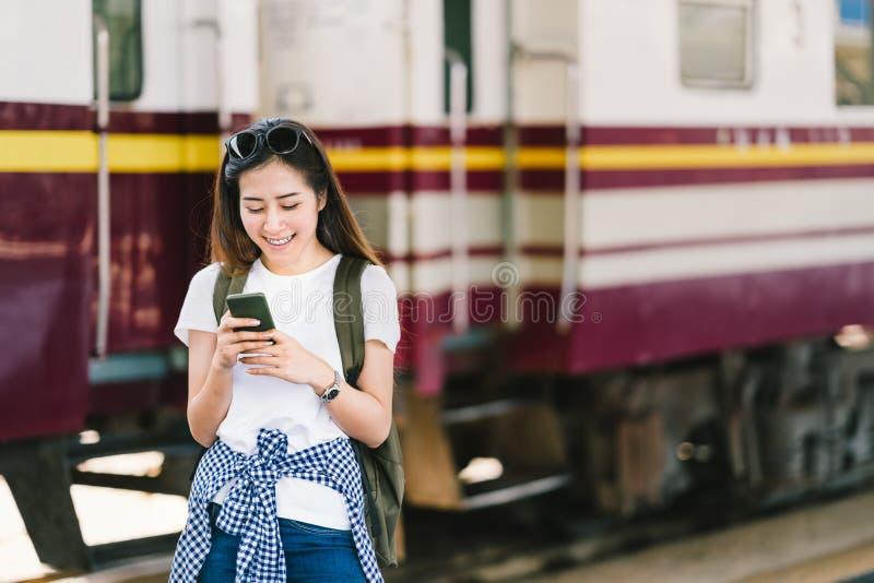 Le voyageur féminin asiatique, la belle femme employant la carte ou le media social arrivent sur le smartphone à la plate-forme d photo libre de droits
