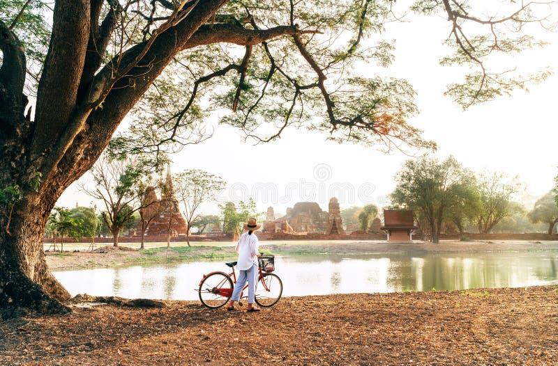 Le voyageur féminin weared les vêtements légers d'été et le chapeau ont la promenade de début de la matinée avec la bicycl photo libre de droits