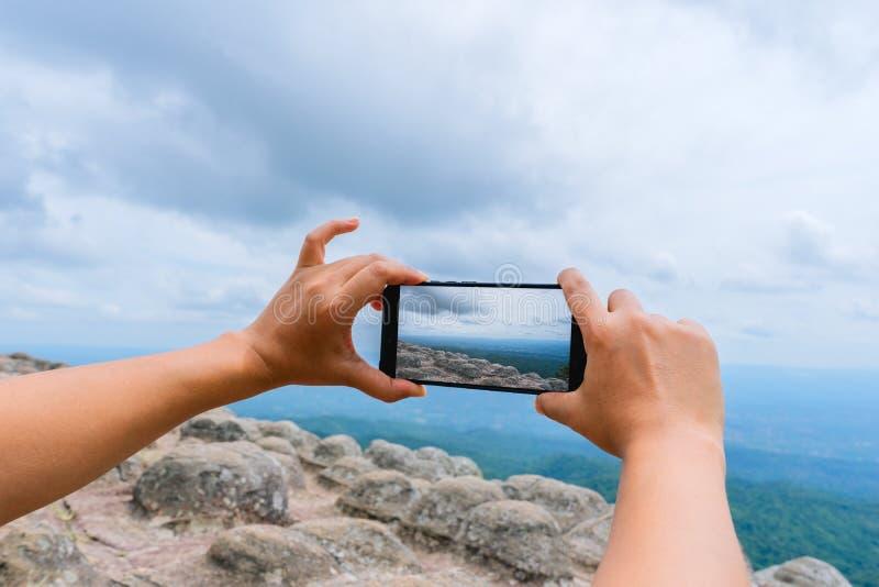 Le voyageur font la photo sur le smartphone, utilisant le téléphone à disposition, le blogger de voyage, fin du women& x27 ; main photos stock