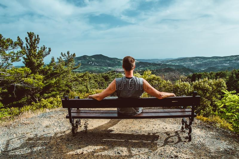 Le voyageur, homme barbu s'assied sur un banc Jour ensoleillé dans les montagnes Parc national Troodos, Chypre images stock