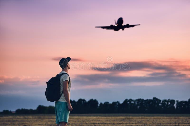 Le voyageur regarde l'avion d'atterrissage images stock