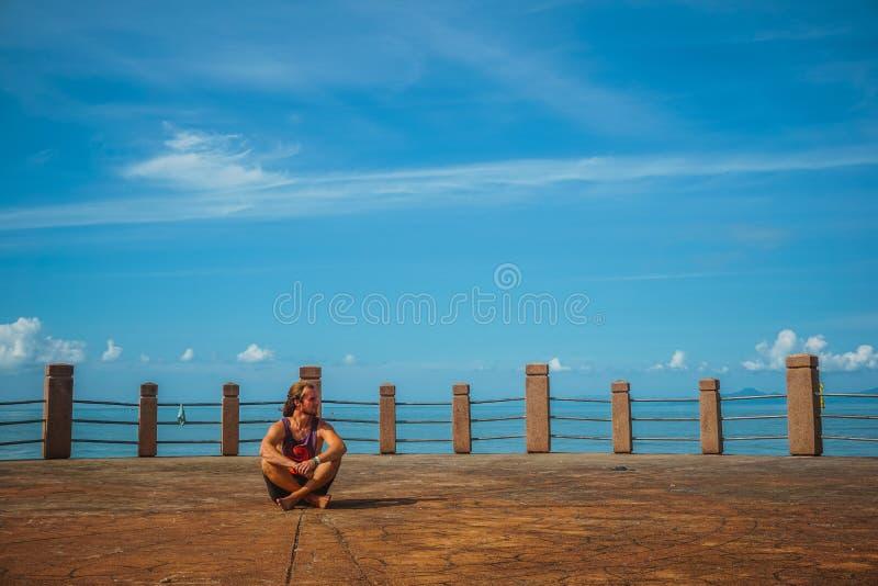 Le voyageur s'assied sur le bord de mer photographie stock libre de droits
