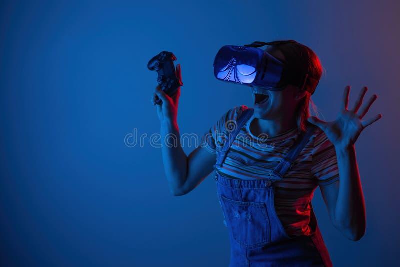 Le vr de jeu La fille dans le casque et le contrôleur joue un jeu avec la lumière créative concept des sports de cyber gibiers vi images libres de droits