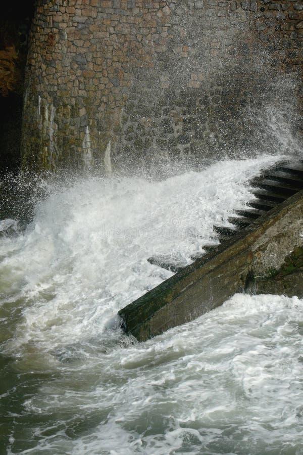 Le WhiteWater des vagues se précipite vers le haut des étapes de bord de la mer au-dessous du mur en pierre illustration de vecteur
