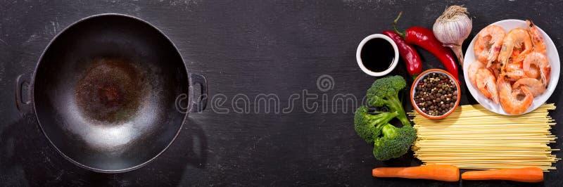 Le wok vide avec des ingrédients pour faire cuire l'émoi a fait frire des nouilles avec s photo libre de droits