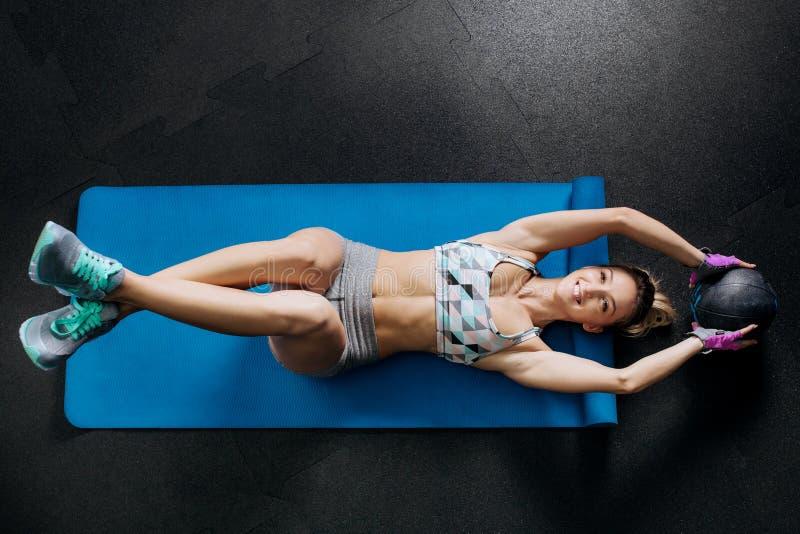 Le womanwith de forme physique que beau faire de sourire se reposent lève des exercices abdominaux de noyau de craquements d'ABS  photographie stock libre de droits
