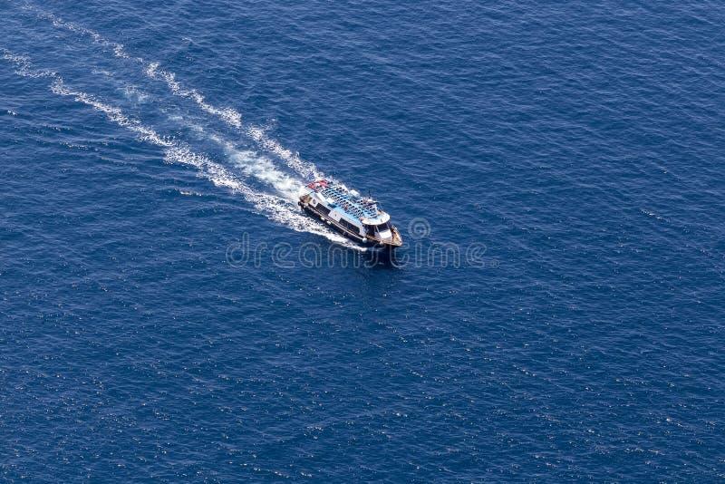 Le yacht dirige dans la belle eau bleue près de l'île de Santorini, photo libre de droits