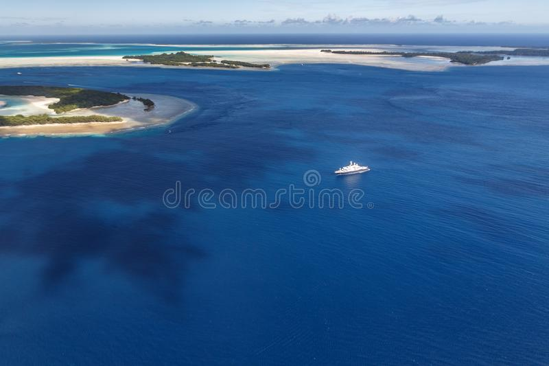 Le yacht méga bleu et blanc glisse parmi les îles tropicales dans les eaux Pacifiques photo stock