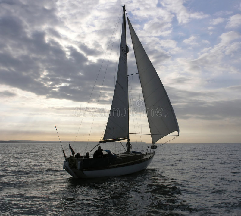 Le yacht navigue en soirée photo stock