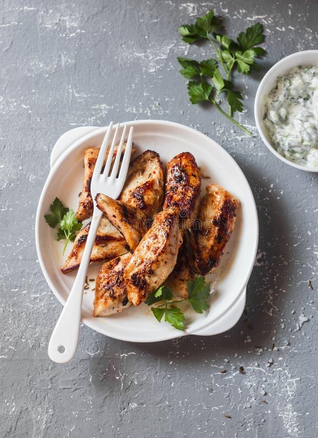 Le yaourt mariné a grillé le blanc de poulet sur un fond gris images libres de droits