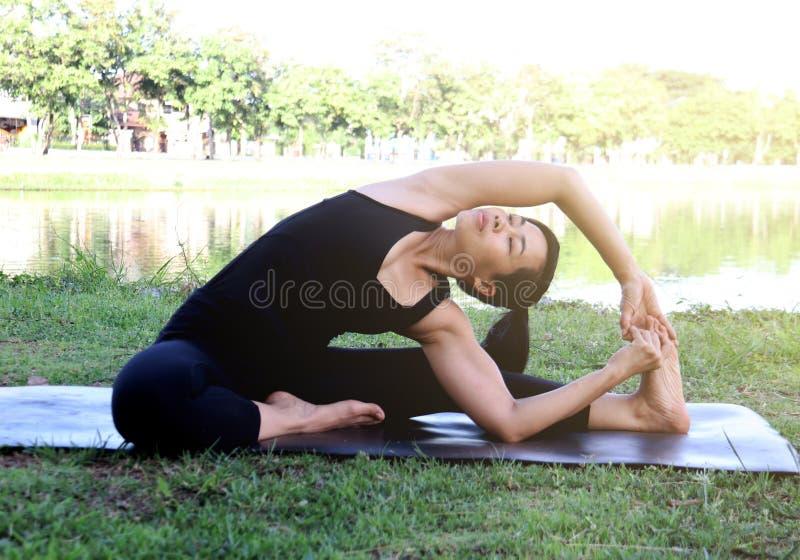 Le yoga asiatique d'exercice de femme extérieur, tournent la pose de tête-à-genou photos libres de droits