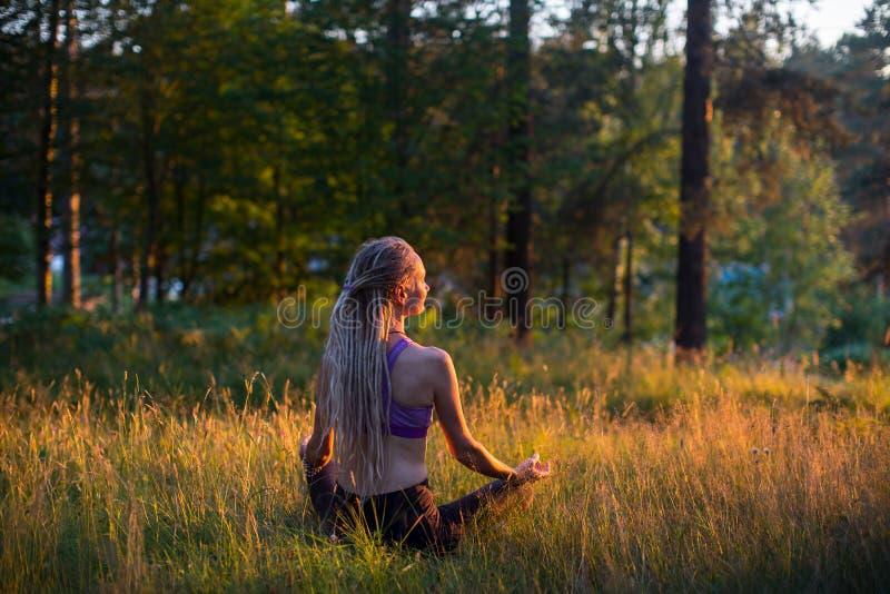 Le yoga de femme avec de longs dreadlocks de cheveux médite sur la nature détendez photos libres de droits