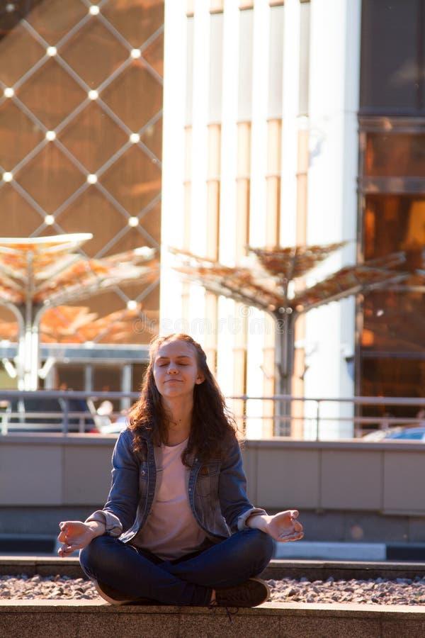 le yoga de jeune fille et médite en position de lotus dans une grande ville images libres de droits