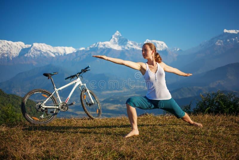 Le yoga de pratique de femme, détendant après la monte fait du vélo photo libre de droits