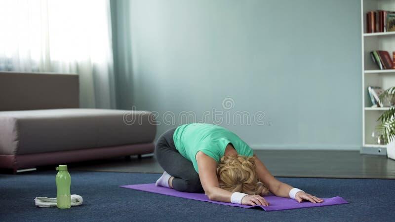 Le yoga de pratique de femme mûre sportive pose la maison, la forme physique et la santé, s'étendant photos libres de droits