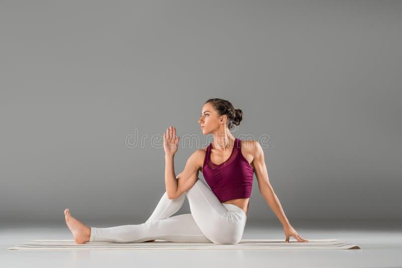 le yoga de pratique de femme, se reposant dans le demi seigneur des poissons s'exercent, Ardha photographie stock libre de droits