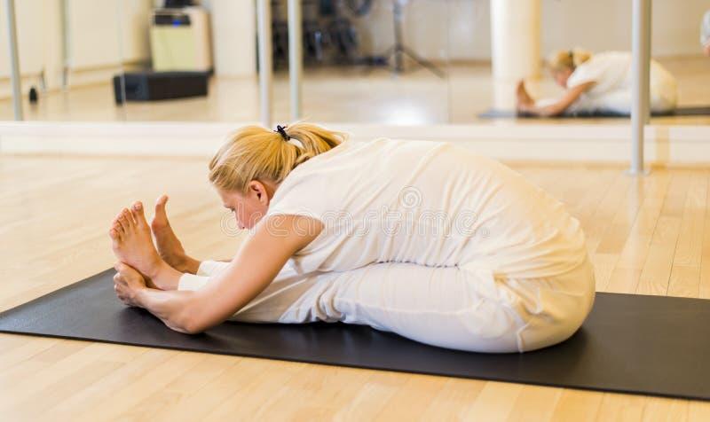 Le yoga de pratique de femme se reposant dans Paschimottanasana a posé Forwa images libres de droits
