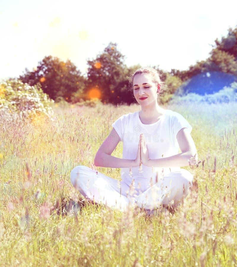 Le yogaflickan som mediterar för glad reträtt, färgrikt retro filter royaltyfri foto
