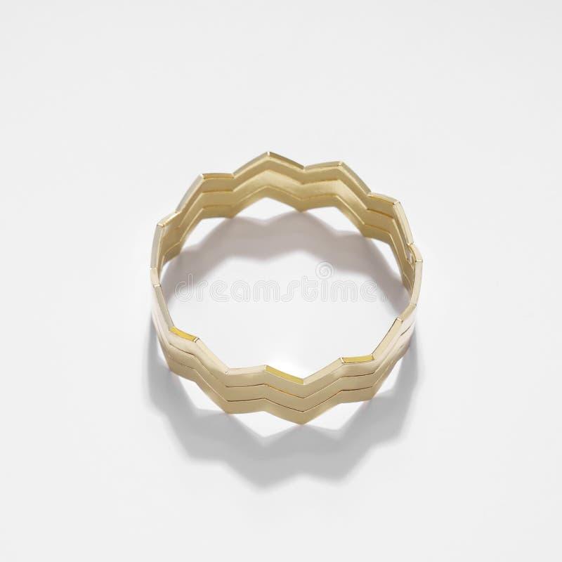 Le zigzag d'or moderne a formé le bracelet d'isolement sur le fond blanc image stock